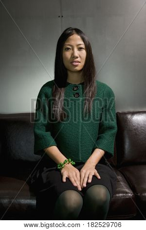 Asian woman sitting on sofa