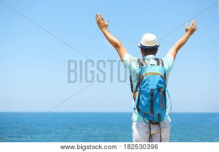 Happy man raised arms on summer beach. Travel and vacarion concept