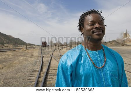 African man walking along train tracks