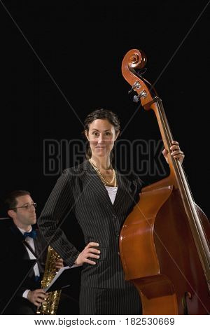 Woman in suit holding upright bass
