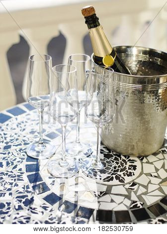 Champagne bottle and four flutes on the table at outdoor celebration party