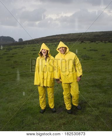 Hispanic couple in rain gear holding hands