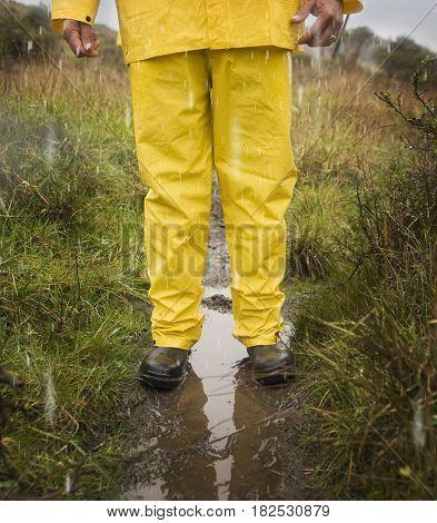 Hispanic man in rain gear standing in puddle