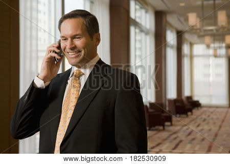 Businessman talking on cell phone in corridor