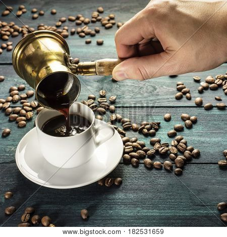 A square photo of strong coffee being poured from a vintage coffee pot into a white porcelain cup, on a dark background with scattered coffee beans and copyspace