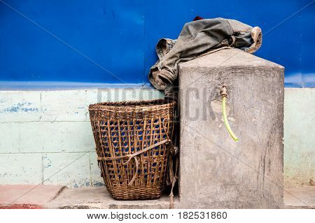 Traditional Nepali basket used to carry items up and down mountian paths layed to rest alongside a water source in one of the villages found on trekking routes in the Annapurna region. Ghorepani.
