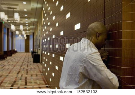 African businessman with head against wall