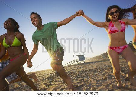 Multi-ethnic group of friends running on beach