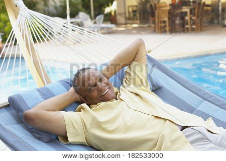African man laying in hammock at poolside