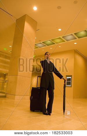 African businesswoman with suitcase talking on cell phone in lobby
