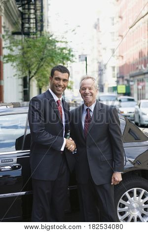 Businessmen shaking hands in front of limousine
