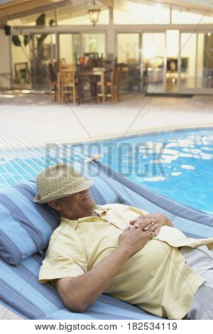 African man sleeping in hammock at poolside