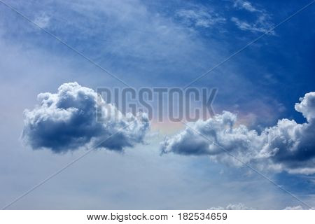 Blue sky with white clouds and rainbow.