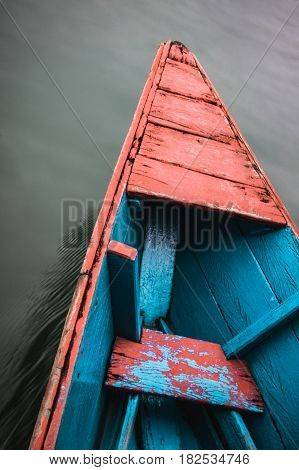 The front of a colourful wooden canoe cuts through the still water of Phewa (Fewa) Lake in Pokhara Nepal.