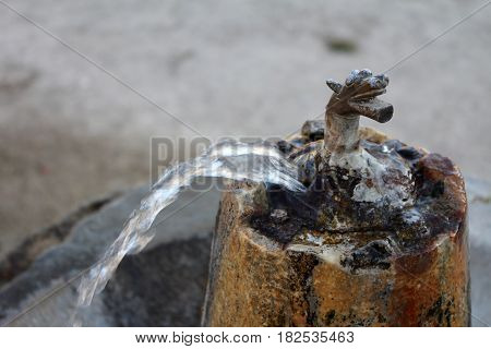 Old Vintage bronze drinking fountain on a stone basement outdoors