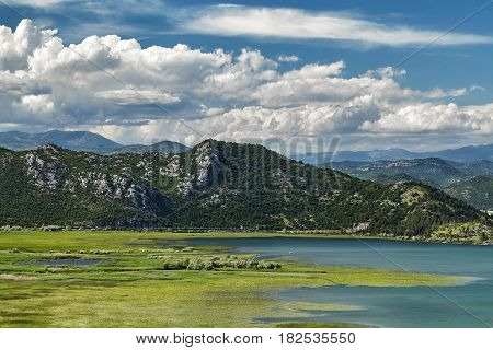 Panoramic view of Skadar lake at the Montenegro part travel destination. A sunny day in the Skadar lake bay national park and one of the beautiful places on Montenegro, Europe. Close-up of a mountain