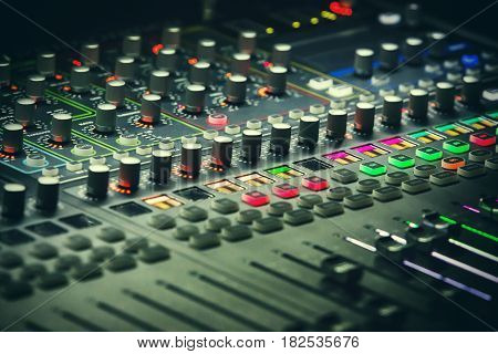 Music mixing console with backlit buttons. Audio mixer mixing board fader and knobs