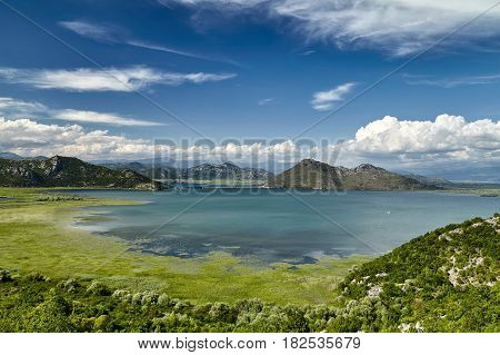 Panoramic view of Skadar lake bay at the Montenegro part travel destination. A sunny day in the Skadar lake with mountains is a national park and one of the most beautiful places on Montenegro, Europe