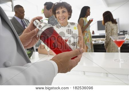 Host mixing martini cocktails at party