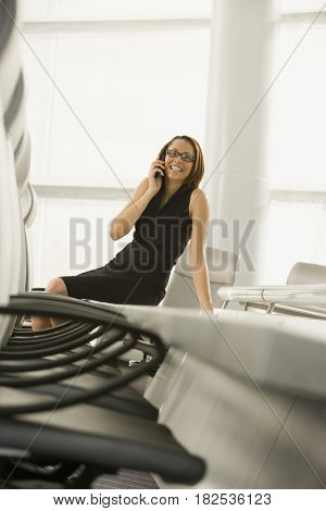 African businesswoman talking on cell phone in conference room