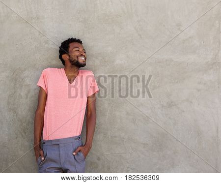 Attractive Afro American Man Leaning Against Wall Smiling