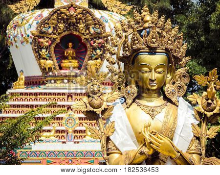 Close up detail of statues and stupa at Kopan Monastery temple garden in Kathmandu Nepal.