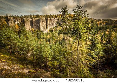 Tall pines in autumn mountains scenery. Steep ridges of Skalni Mesto in Czech National Park. Beautiful colorful fall trees painted in yellow gold red and green. Dramatic cloudy sky adds climate to the scene