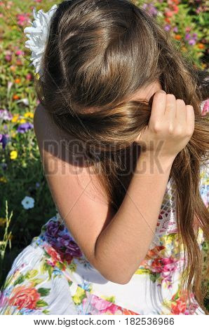 young lonely woman sitting on grass at the meadow in summer day