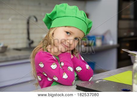 Girl in a green cap in the kitchen