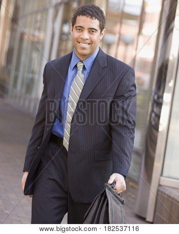 Mixed race businessman holding briefcase