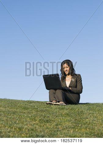 Mixed race businesswoman using laptop in grass
