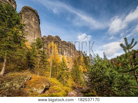 Colorful autumn mountain valley in czech national park - Slalni Mesto. Steep mountains grow out from beautiful yellow gold red and green fall forest