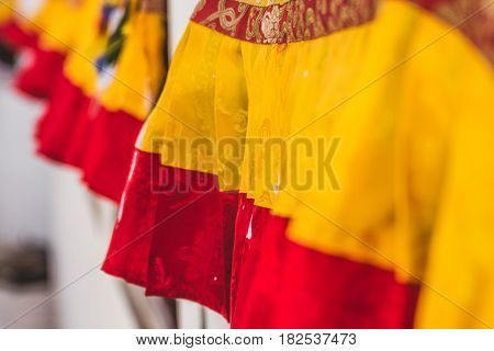 Close up detail of decorative yellow and red flags used to cover prayer wheels at the base of Boudhanath stupa Kathmandu Nepal.