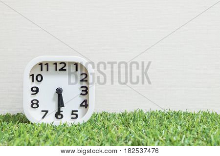 Closeup white clock for decorate show a half past five o'clock or 5:30 p.m. on green artificial grass floor and cream wallpaper textured background with copy space
