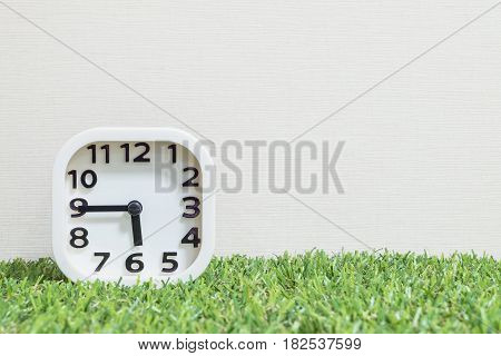 Closeup white clock for decorate show a quarter to six o'clock or 5:45 p.m. on green artificial grass floor and cream wallpaper textured background with copy space