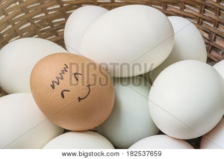 Closeup brown chicken egg with paint in smile face on pile of white duck egg on wood basket background