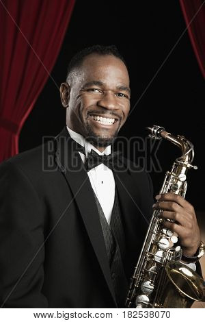 African American man in tuxedo posing with saxophone