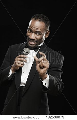 African American man in tuxedo holding microphone and gesturing