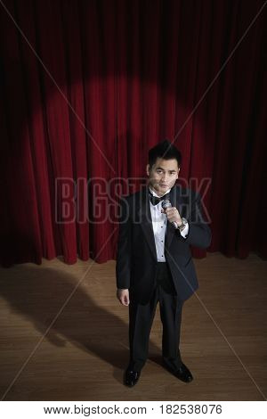 Asian man in tuxedo holding microphone onstage