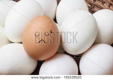 Closeup brown chicken egg with paint in tried face emotion on pile of white duck egg on wood basket background