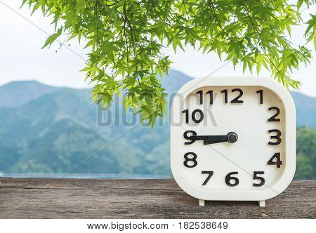 Closeup white clock for decorate show show a quarter to nine o'clock or 8:45 a.m. on blurred green leaves and mountain view background