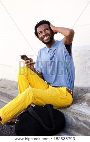 Smiling Man Sitting And Holding Smart Phone With Bag