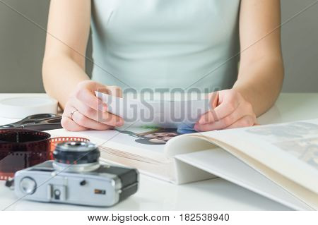 Young female person holds photo print in hands. Married or engaged girl in dress sits at white desk with film camera and film strip and puts printed photographs into family album