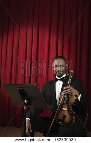 African American man in tuxedo onstage with violin