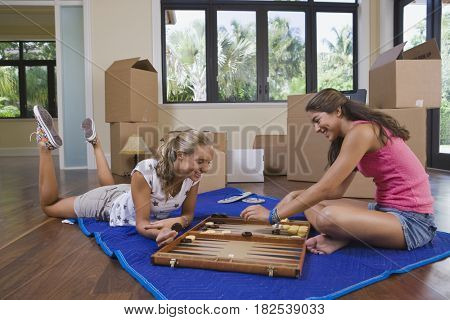 Hispanic teenage girls playing backgammon