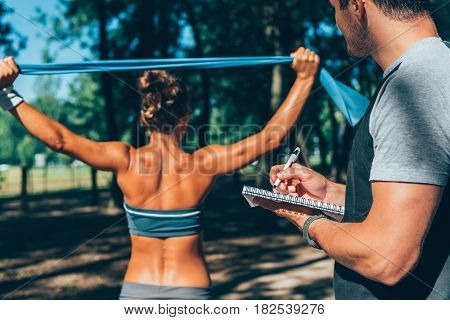 Exercising with resistance band in training outdoors, color image