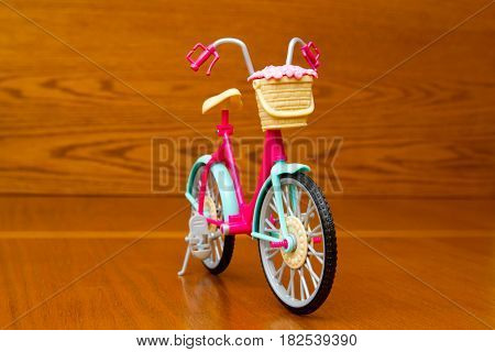 A toy bicycle on a brown background macro photo