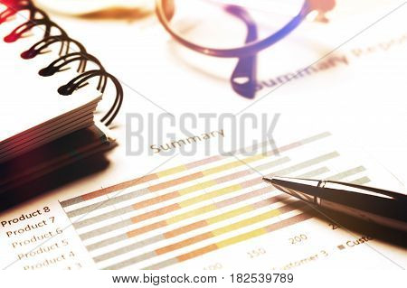 Summary Report And Financial Analyzing Concept, Pen And Notebook And Eyeglasses On Paper Report.