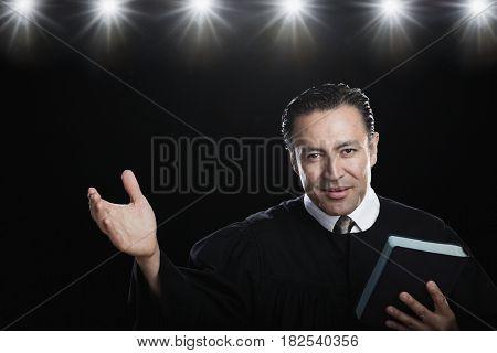 Hispanic man holding Bible and gesturing