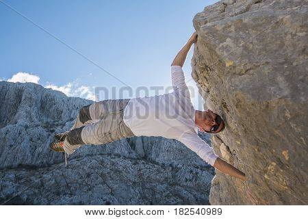 Young man climbing rock wall and hanging above gap. Roao Villanueva del Rosario Malaga